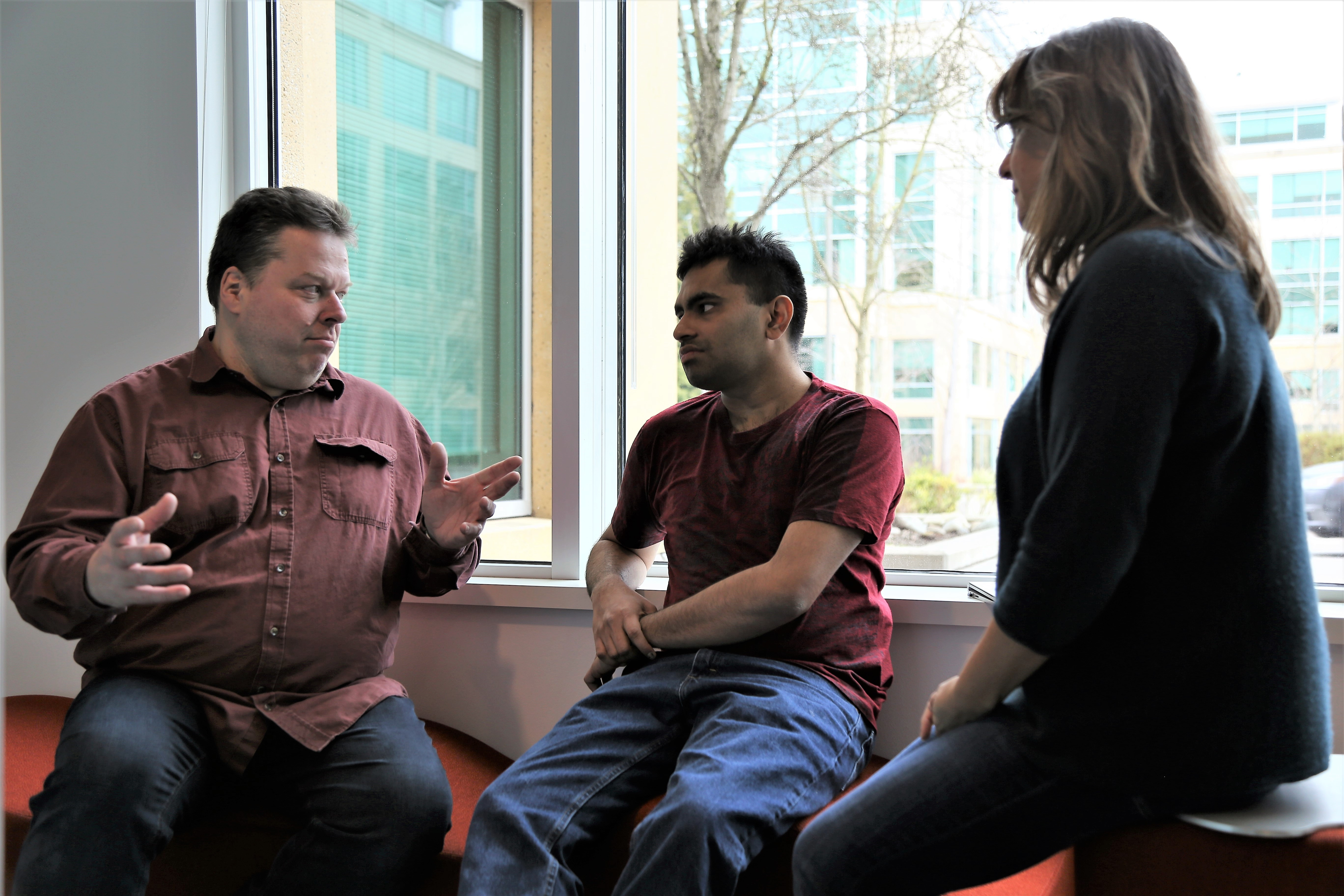 Hans Reutter talks with members of his team while sitting in front of a window in a common space area in his building.