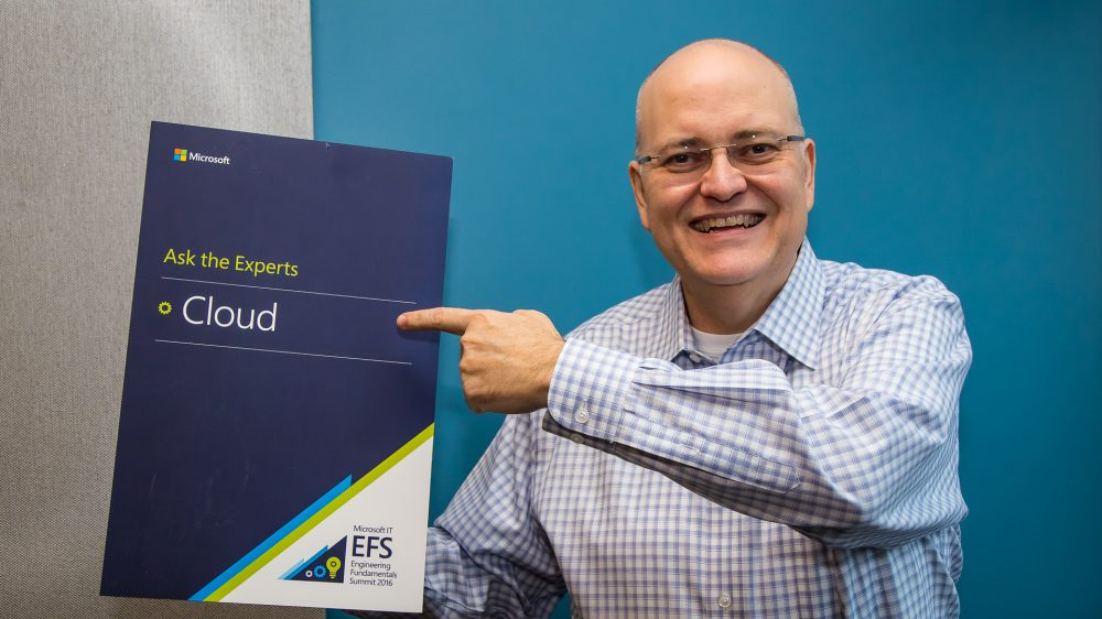 Apple holds up and points to a Microsoft cloud brochure while smiling at the camera.