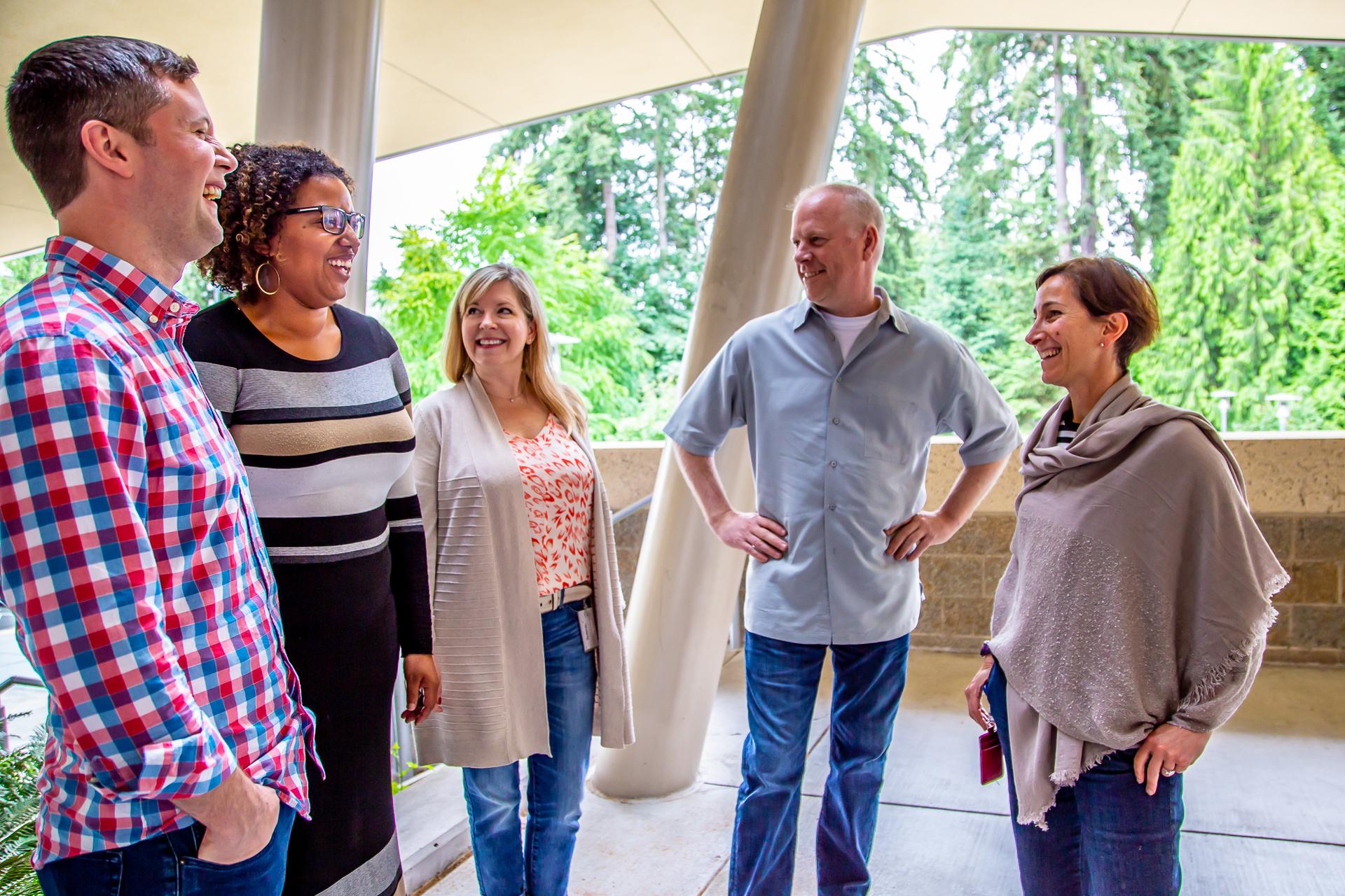 Bill Lincoln, Cassandra Young, Rebekah Hankins, Kurt Hughes, and Liz Friedman share a laugh in a photo taken outside.