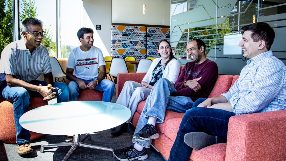 The Microsoft blockchain project share a light moment at their offices on the Microsoft campus. They are sitting on a coach outside in a common space. From left-to-right, Rohit Amberker, Siddharth Pandey, Katie Lencioni, Jagannathan Venkatesan, and Dmitrii Fotesco.