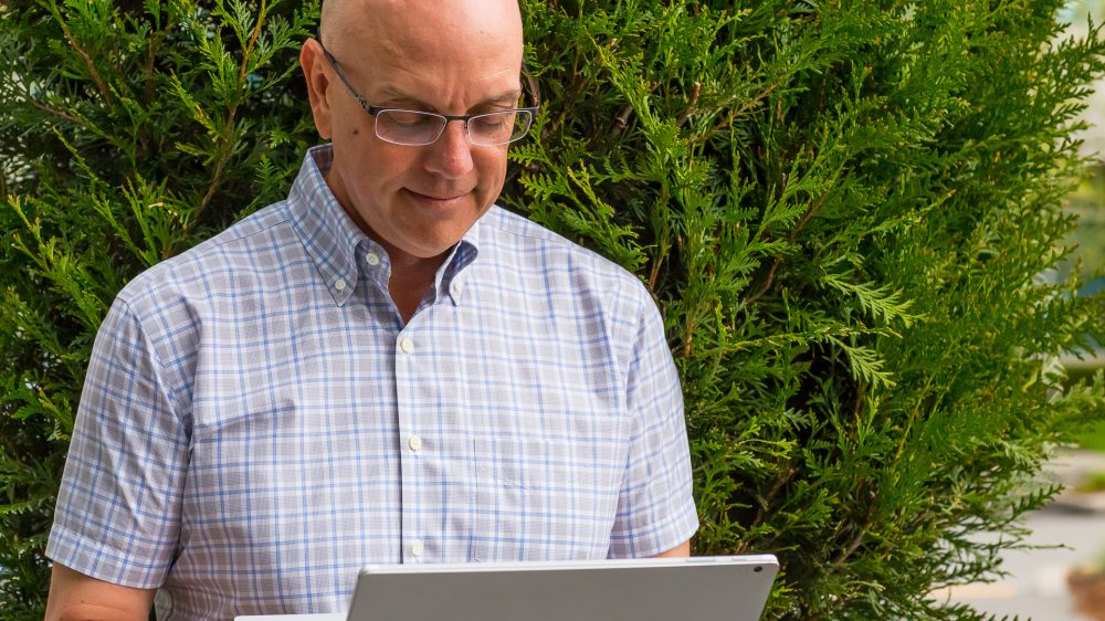 Chad Dellinger looks down at his laptop outside in front of some greenery.
