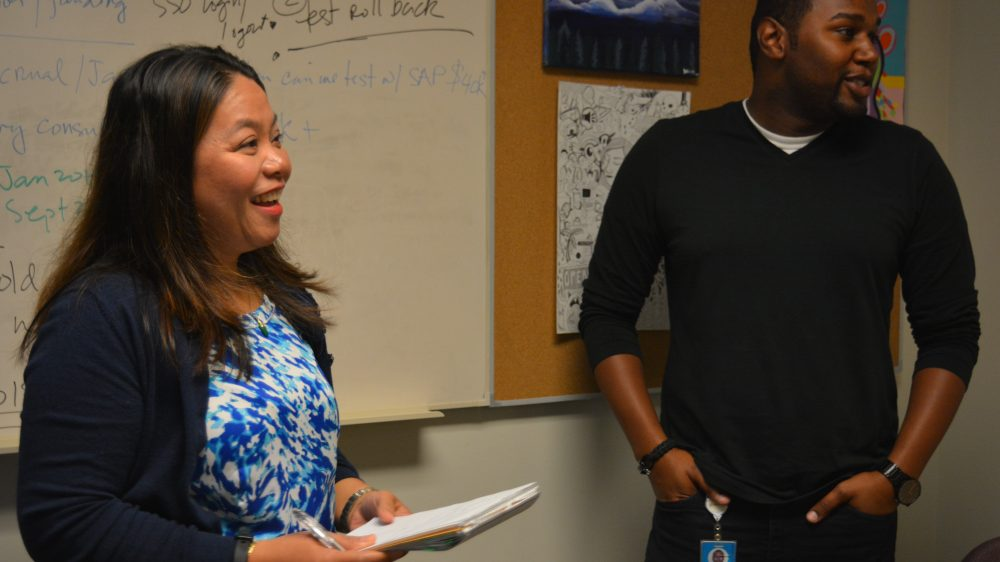 Helen Valmeo-Yang and DeShawn Ellis stand and talk in front of a whiteboard and corkboard with art as they talk to someone off-camera