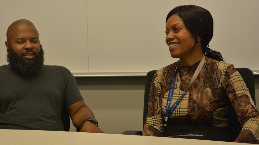A smiling Katina Reece sits at a table in a conference looking toward the camera. She's talking with colleague Bryan Griffin.