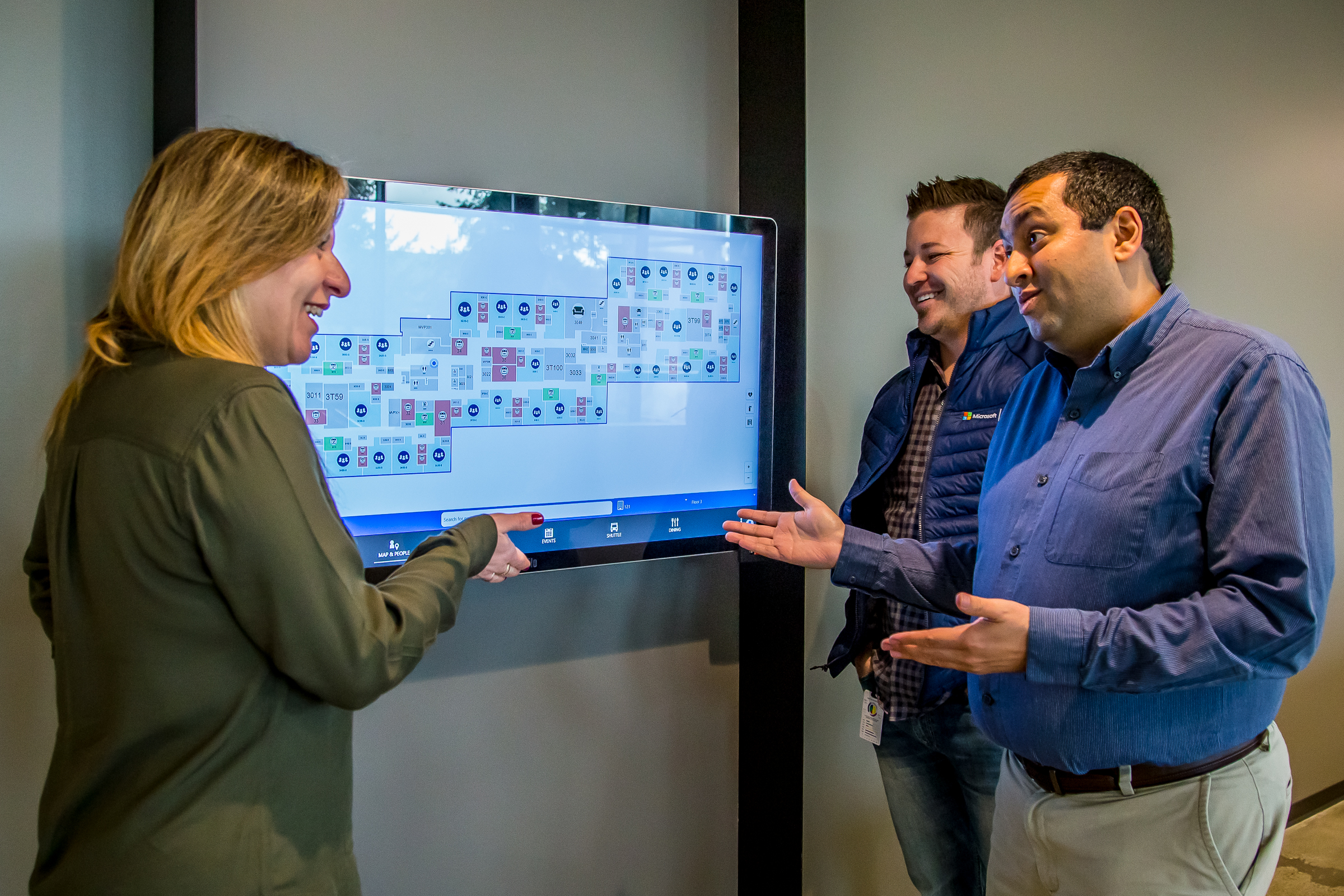 Kelly Monteiro and Pankaj Arora both gesture at a new smart building kiosk mounted on a wall in the stairwell of Building 121. Weston Henderson looks on.