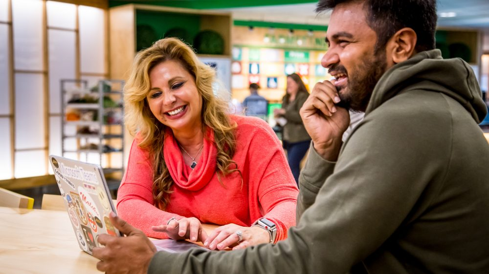 Pouneh Kaufman and Mohammed Anas Shaikh share a laugh sitting at a table in a Microsoft cafe.