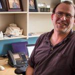 David Johnson sits at his desk smiling at the camera.