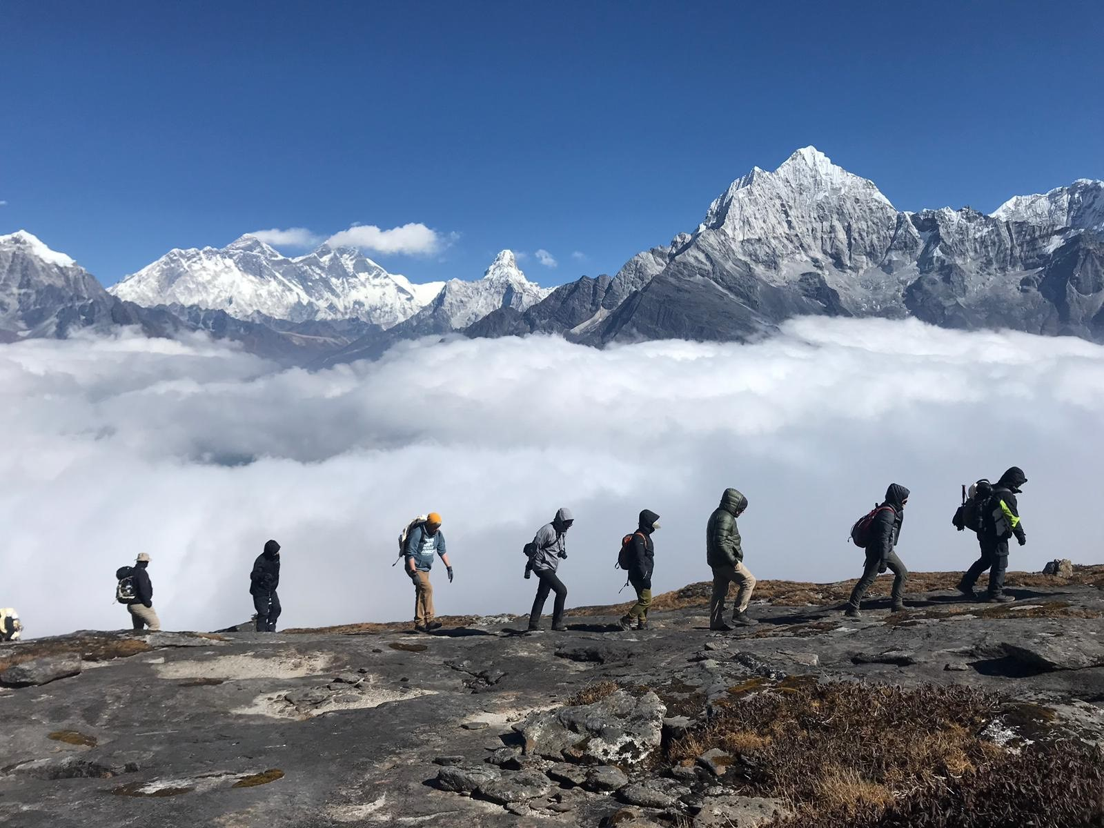 A group of Microsoft employees climb along a ridge withe the Himilayan Mountains in the background. They are in a single file line walking on a rock ridge.