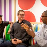 Shiran Sathananthan, Brent Schnabel, and Joseph Jassey sit at a couch talking with each other.