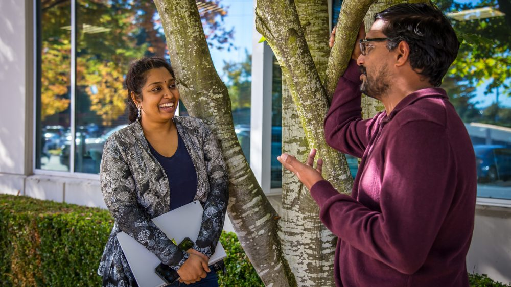 Aparna Chadalavada and Krishna Vemuri talk together outside of a building on the Microsoft campus.