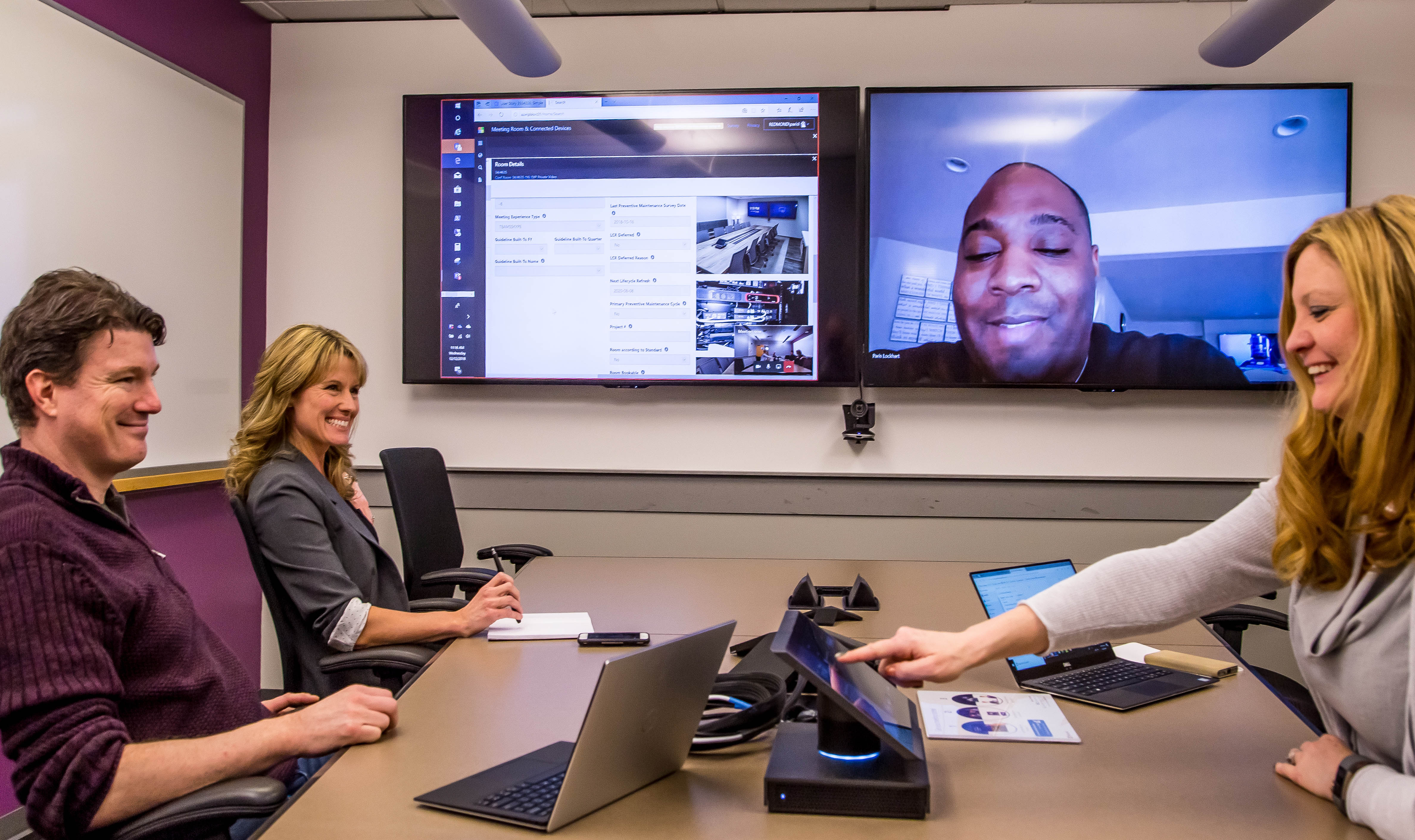 CSEO's Matt Hempey, Jaimie Faccone, and Stacie Kartes chat in a meeting room as Paris Lockhart joins them online via a large screen on the wall.