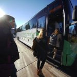 Microsoft employees walk onto a Connector bus on a sunny day,