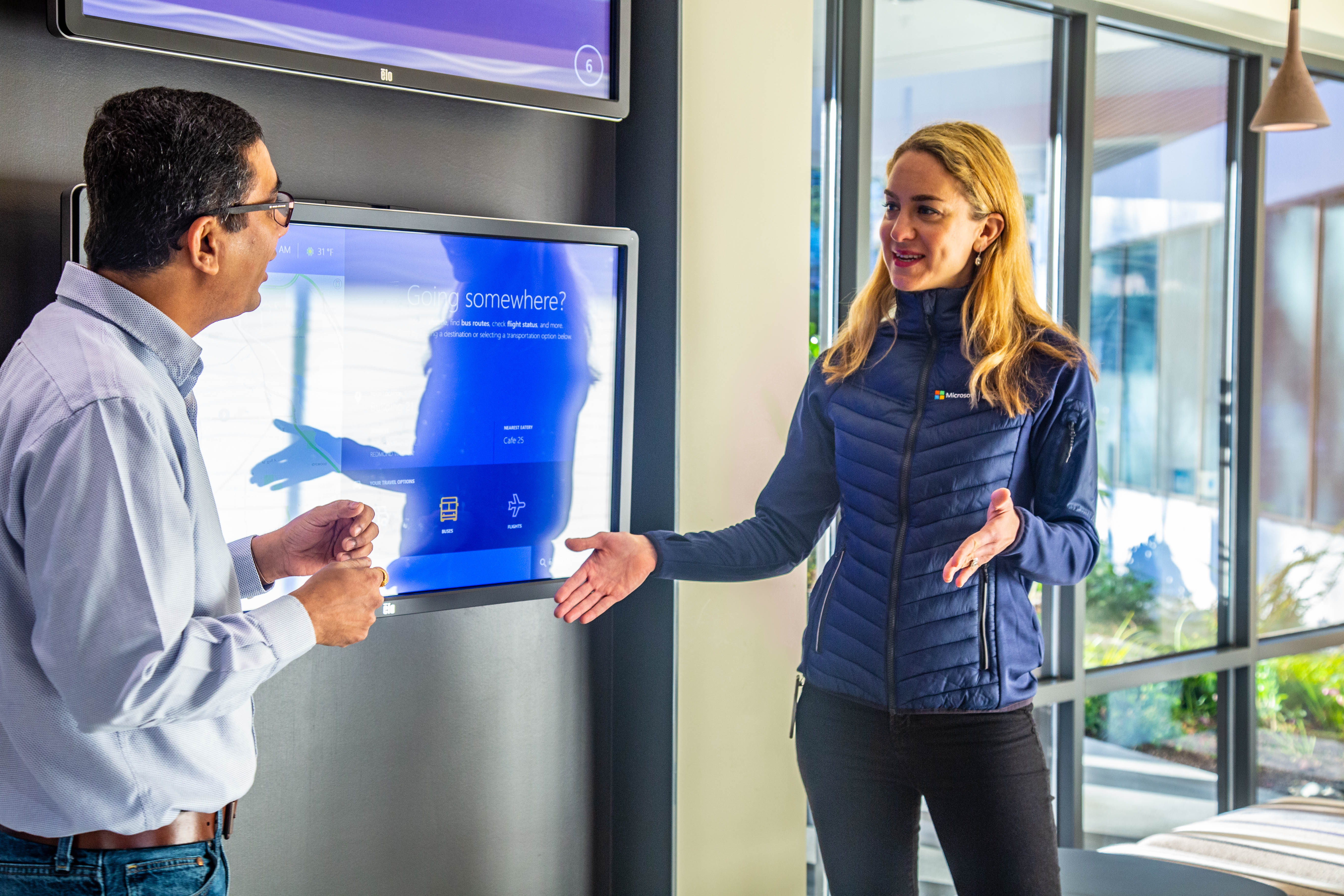Vishu Admal and Esther Christoffersen demo a lobby experience departure module in Microsoft Building 21. They are standing in front of the screen that they can use to book a shuttle and get other information about how to get to another building.