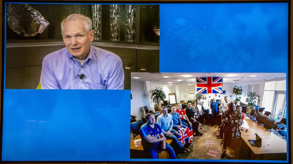 This photo shows a split-screen view, with Kurt DelBene on one screen answering a question posed by the United Kingdom team, which appears on the second screen.