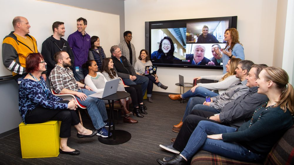 Pouneh Kaufman speaks to the team that led the upgrade to Microsoft Teams across Microsoft. Kaufman is standing in front of a Surface screen. The team sits on chairs and benches on either side of the Surface. Four team members have joined the meeting via Teams and are showing on the Surface screen.