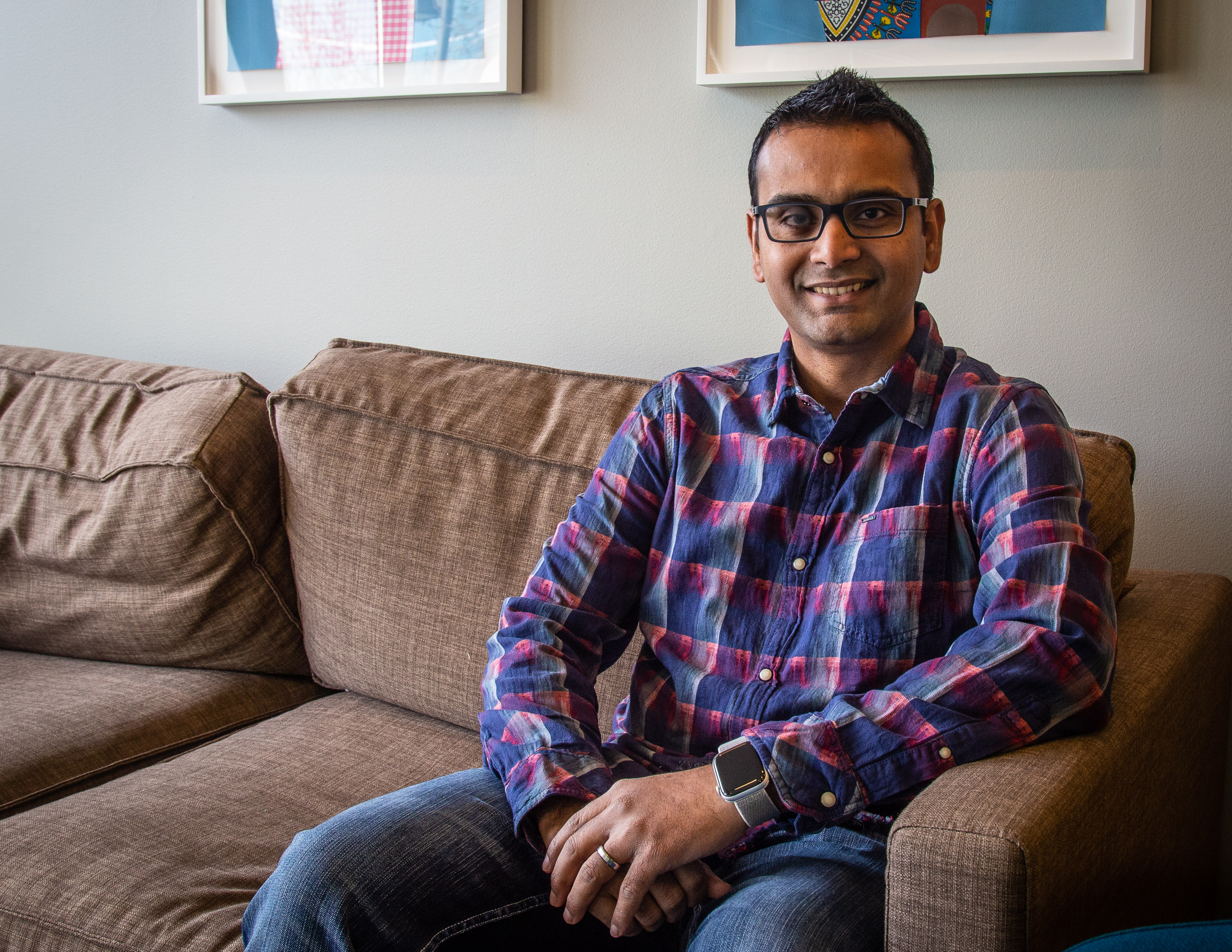 Abu Kabir sits on a couch in an open space near his office at Microsoft.