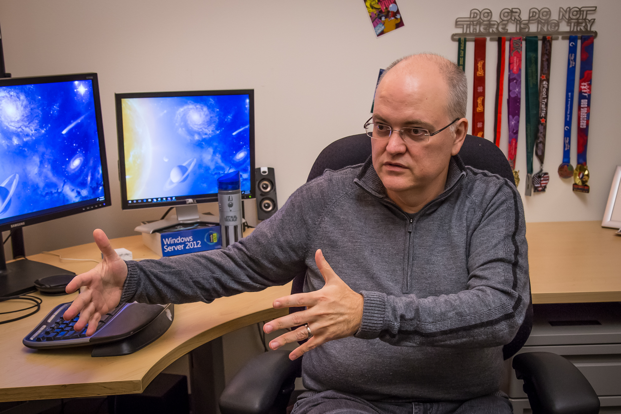 Pete Apple sits at his desk in his office, gesturing with his hands as he makes a point to someone