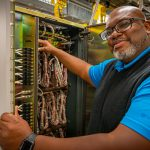 Dwight Jones stands in front of a PBX chassis in the telecom room in Microsoft Building 41.