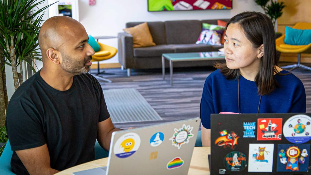 Keshav Puttaswamy and Eileen Zhou sit in a Microsoft open space chatting with each other. They have their laptops open in front of them.