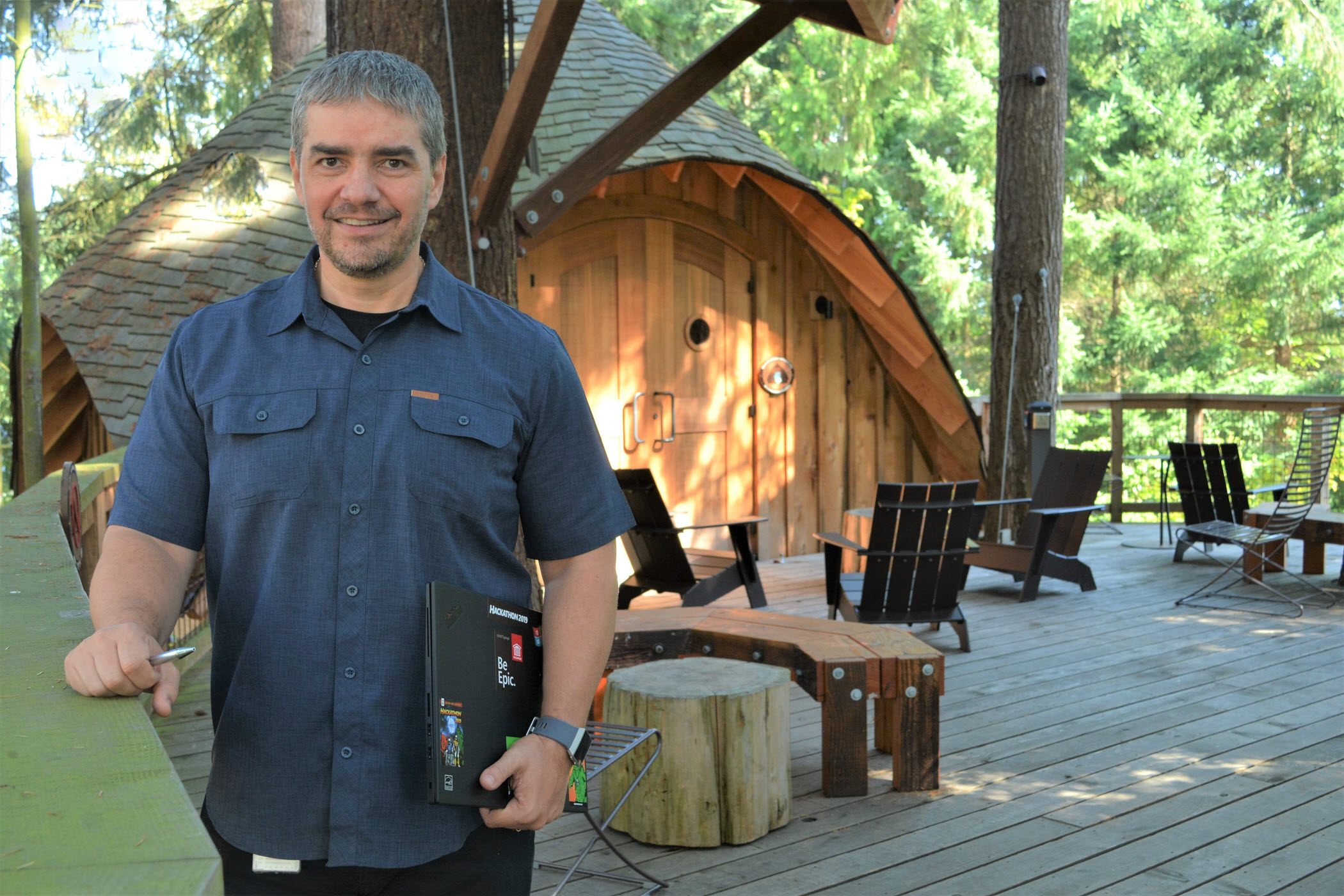 Dan Benedict, looking at the camera, stands with his PC on the balcony of one of the Microsoft treehouses on the company's Redmond campus.