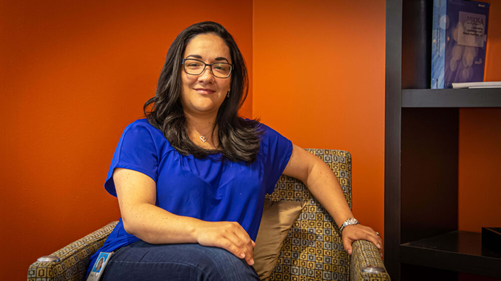Vazjier Rosario looks at the camera while sitting on a couch in an open area near her office on the Microsoft campus.