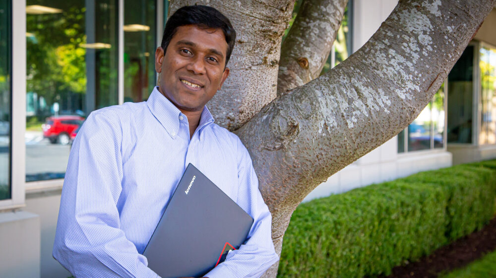 Raja Narayan looks at the camera with his hands holding his PC to his chest. He is standing outside his office on the Microsoft campus.