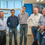 Kurt DelBene and a team of Microsoft employees listen to a presentation on some of the features of the new Microsoft Singapore office. They are standing in an open space near the entrance.