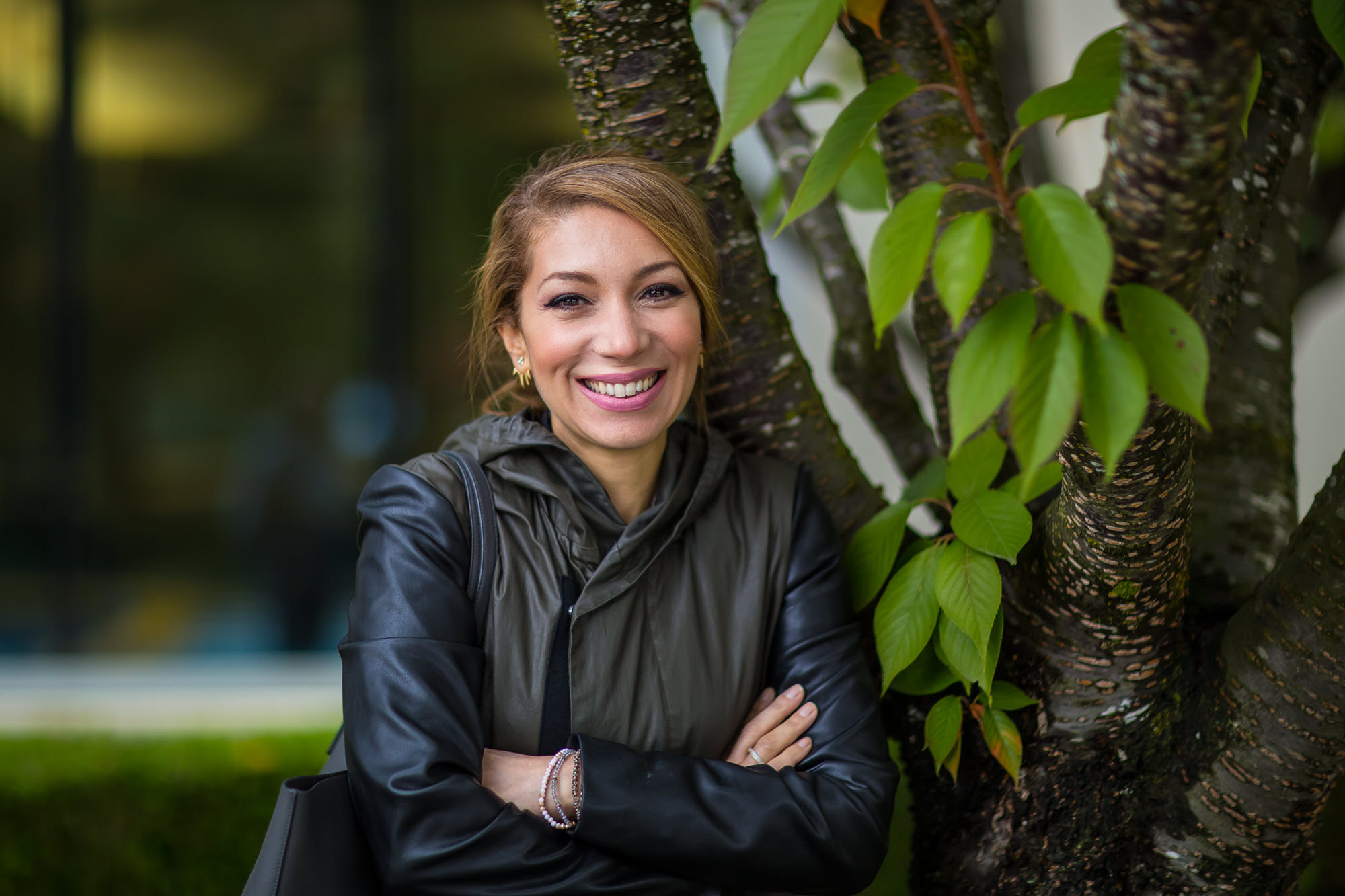 Mina Aitelhadj poses for a photo outside of her Microsoft building. She's leaning up against a tree trunk.