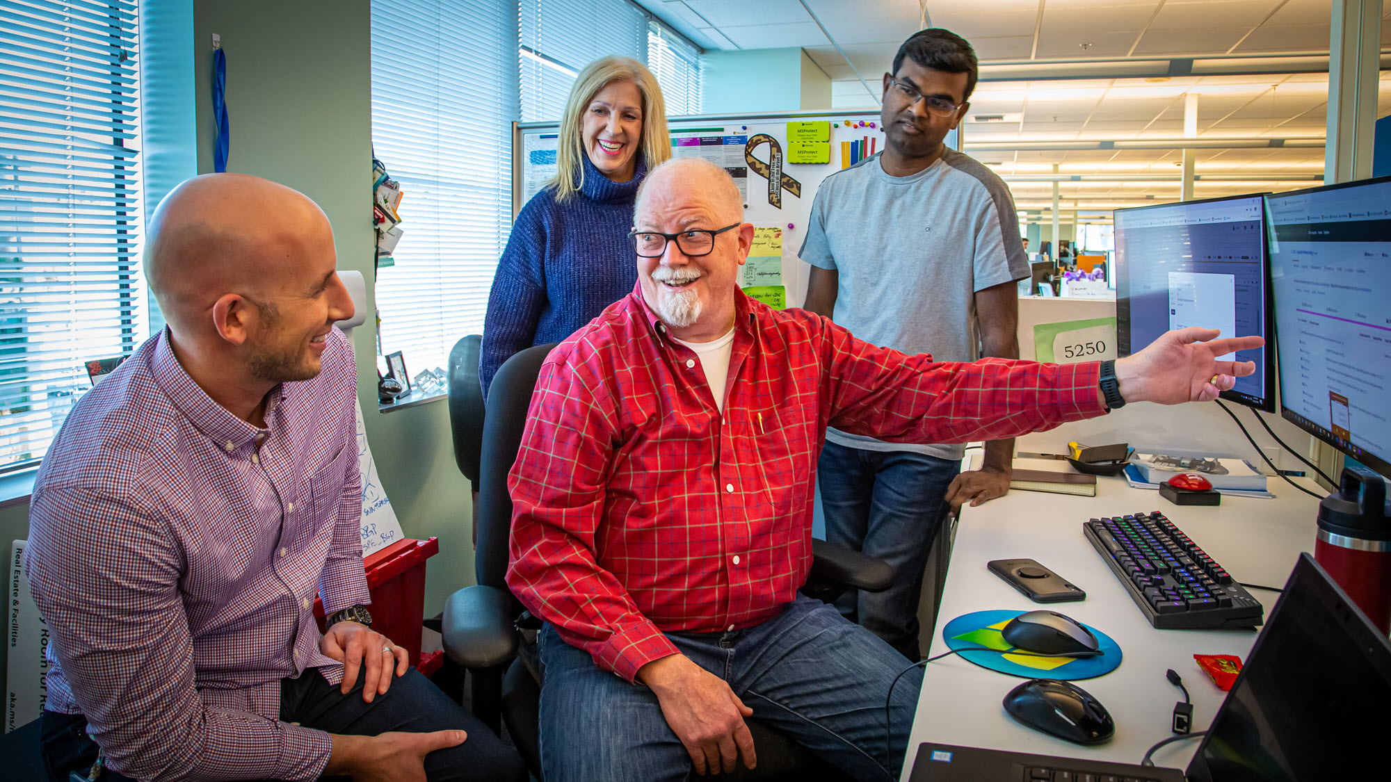 Four Microsoft employees on the Network Automation Delivery Team talk and laugh as Steve Kern gestures to his monitor.