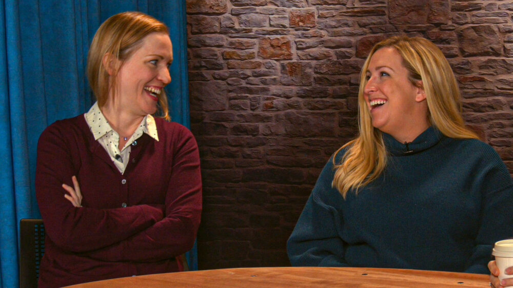 Sarah Lundy and Rachelle Blanchard share a laugh while sitting at a video studio desk on the Microsoft campus.