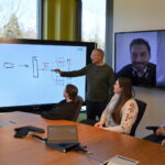 Local and remote members of the Microsoft Invoice Service team meet in a conference room to discuss the Modern Invoice API project. They are collaborating using a digital whiteboard and Microsoft Teams.