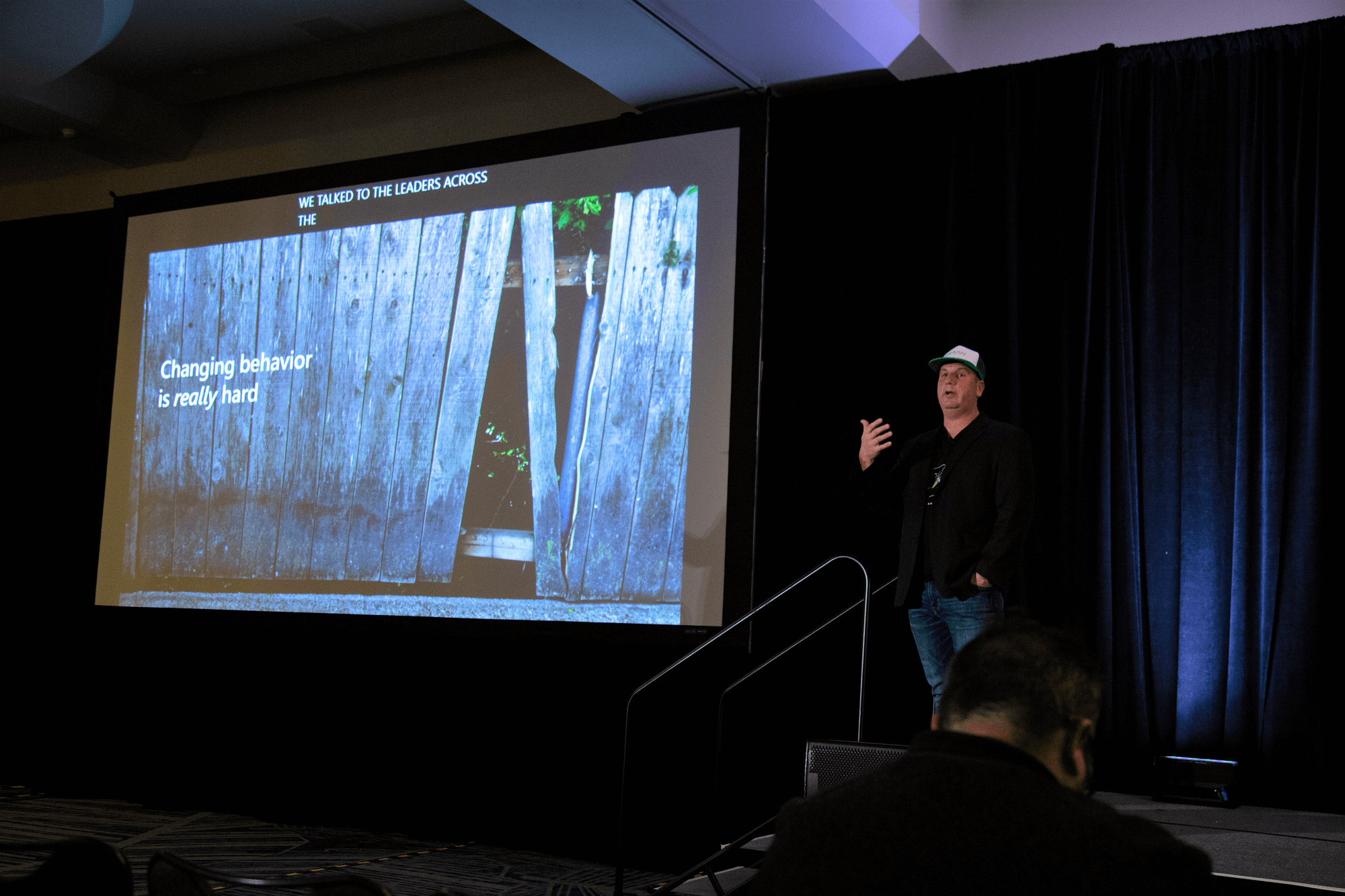 """Ken Sexsmith stands on stage as he gives his Ignite 2019 presentation. The slide reads, """"Changing behavior is really hard."""""""