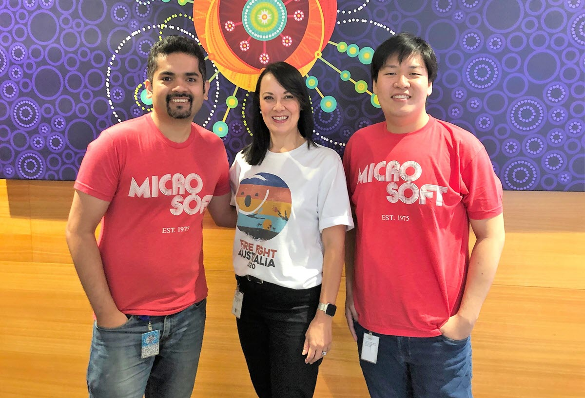 D'Almeida, Deverson, and Liu pose for the camera, with D'Almeida and Liu both wearing original 'Micro-Soft' tee shirts.