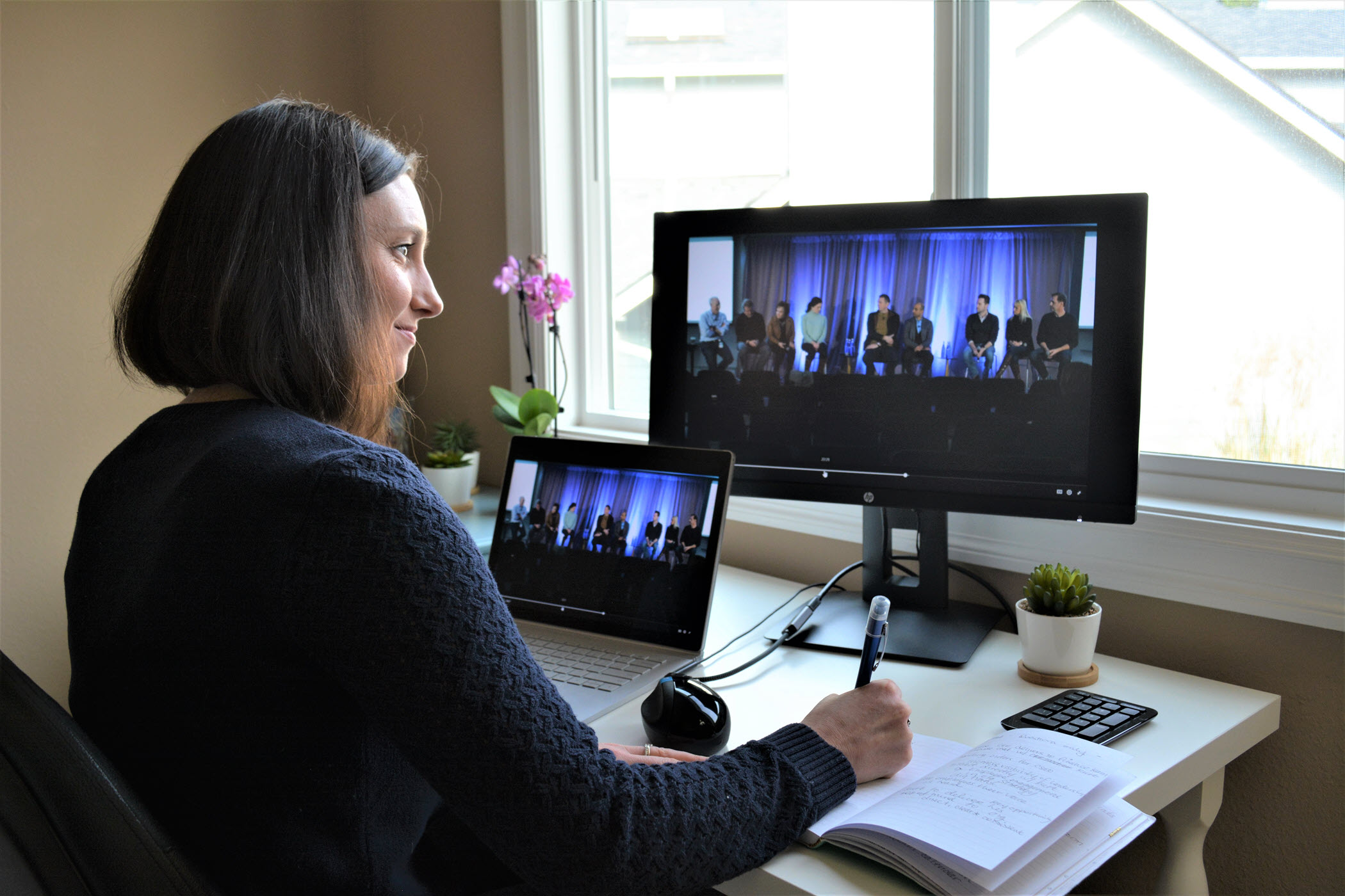 Kimberly Nafziger sits at her desk in her home office. The Ask Me Anything meeting that she's managing is shown on her laptop and monitor.