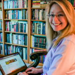 Gina Dyer sits in a library and smiles at the camera while holding her laptop.