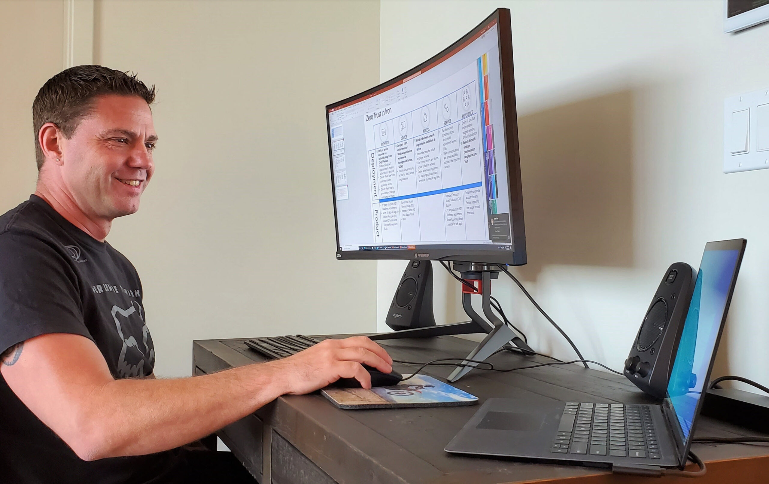 Skorupa sits at his desk and looks at his laptop. His desktop monitor displays a slide on Microsoft's Zero Trust security model.