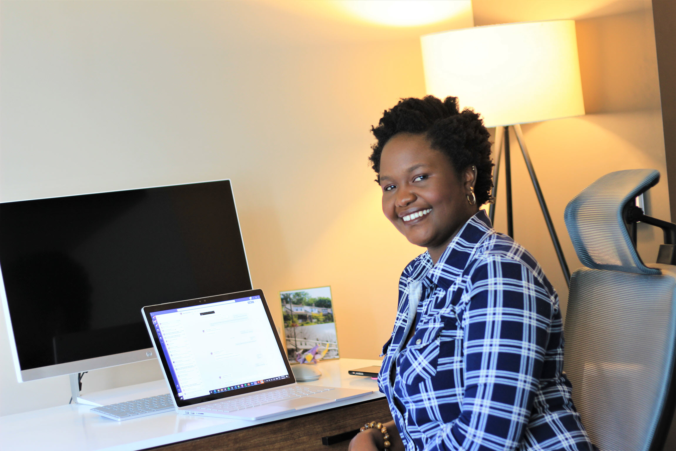 Nyameke sits in front of her laptop and monitor while smiling at the camera.