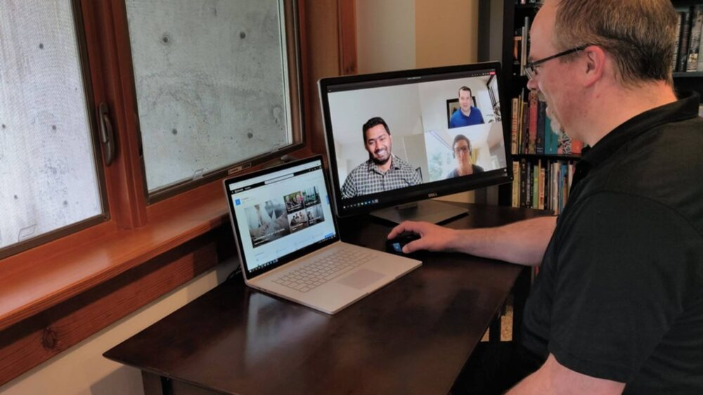 Crewdson participates in a Microsoft Teams meeting from home with a bookshelf in the background, meeting participants displayed on an external monitor, and Microsoft SharePoint displayed on a Microsoft Surface Book 2.