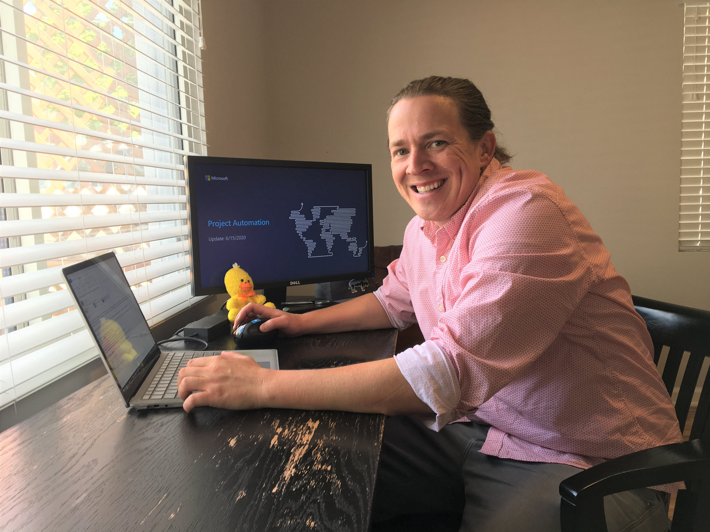 Jeff Cluff looks up and smiles from his desk in his home office.