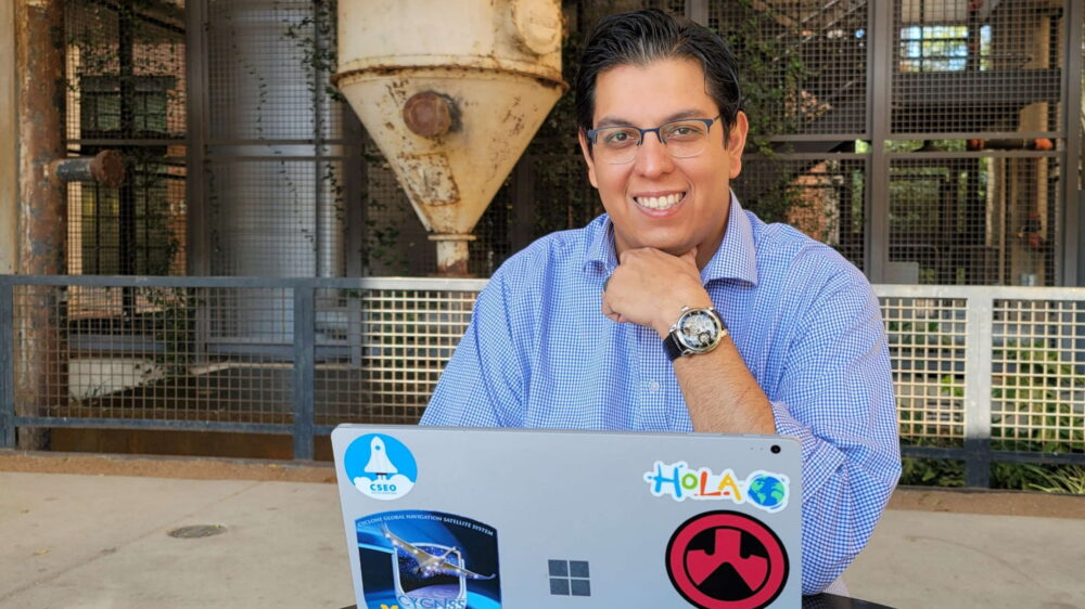 Paul Rojas sits at an outdoor table with his laptop and smiles at the camera.