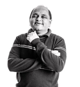 Manish Agrawal smiles as he stands looking at the camera with his arms folded.