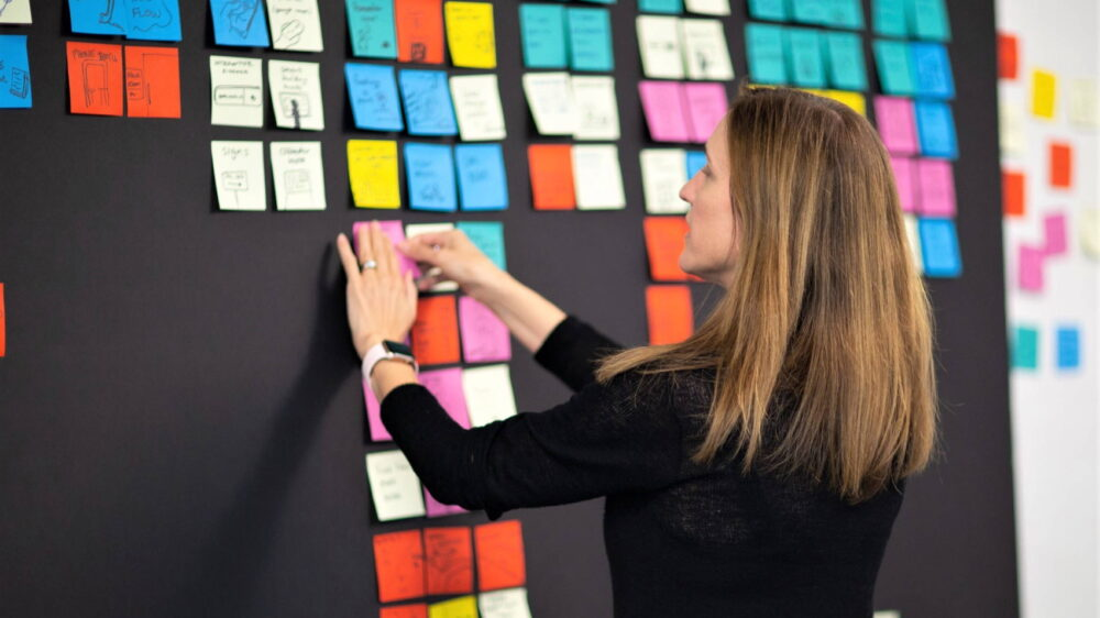 Tricia Fejfar writes on a sticky pad on a whiteboard covered with dozens of sticky pad notes.