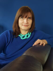 Irina Chemerys relaxes on a chair wearing a sweater and chunky necklace.