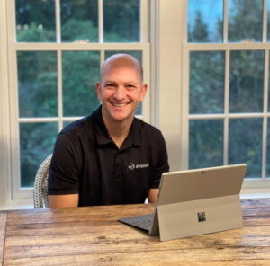 Greg Kriegler smiles while he sits at his computer at home.