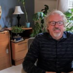 Mike Borth sits at his desk in his home office surrounded by plants.