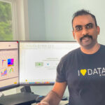 """Kanamarlapudi sits next to a desktop and smiles with a shirt that reads """"I love data."""""""