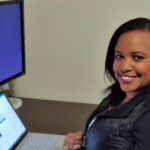 A smiling Chepkwony sits at a desk in a home office working on a laptop.