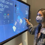 Ansari interacts with the screen of a SmartBuilding services kiosk in the lobby of a Microsoft building.