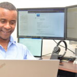 Photo shows Jembere as he works on a laptop computer.