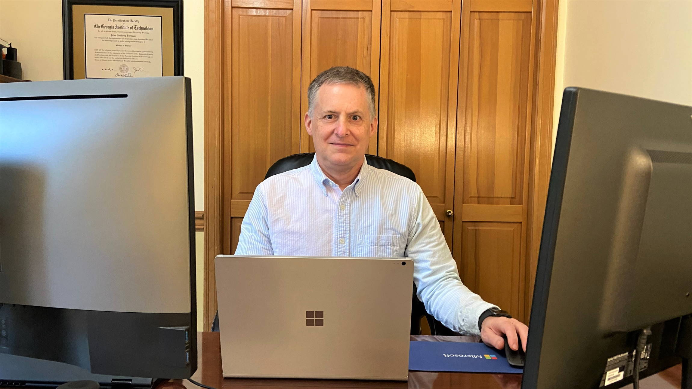 Pete Fortman sits at a desk with two computer screens.