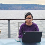 Gaurav, on a back porch overlooking a lake, works from a laptop.